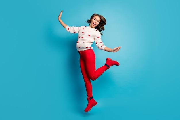 Pełna długość ciała zobacz wesoła, figlarna dziewczyna skacząca, zabawna impreza tematyczna w świątecznych ubraniach