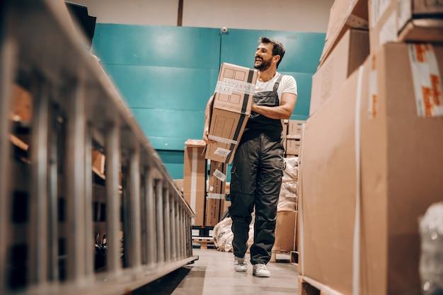 Pełna długość ciężko pracującego pracownika przenoszącego pudełko w magazynie