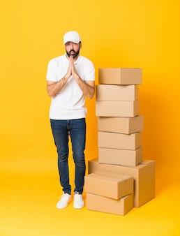 Pełna długość człowieka dostawy wśród pudeł nad izolowaną żółtą ścianą trzyma dłoń razem. osoba prosi o coś