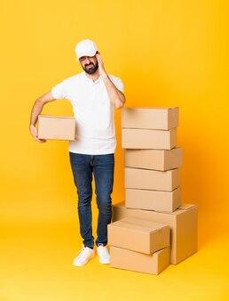 Pełna długość doręczeniowy mężczyzna wśród pudeł nad odosobnioną kolor żółty ścianą z bólem głowy