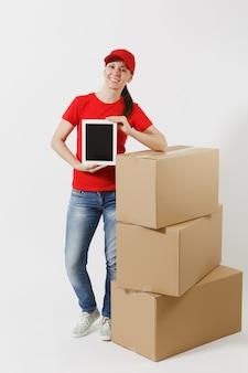 Pełna długość dostawy młoda kobieta w czerwonej czapce, t-shirt na białym tle. kobieta kurier w pobliżu kartonów, komputera typu tablet pc, pusty czarny pusty ekran. odbieranie pakietu. skopiuj miejsce.