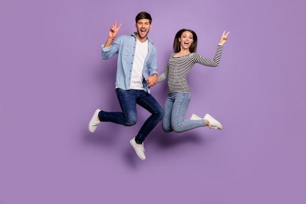 Pełna długość dwóch osób para zabawny facet pani skacząca wysoko trzymając się za ręce pokazujące symbole v-znak noszą stylowe ubranie na białym tle pastelowy fioletowy kolor ściany
