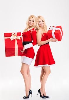 Pełna długość dwóch uśmiechniętych pięknych bliźniaczek sióstr w strojach świętego mikołaja trzymających duże prezenty na białym tle