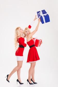 Pełna długość dwóch zabawnych bliźniaczek sióstr w sukienkach świętego mikołaja na białym tle
