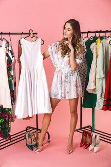 Pełna długość eleganckiej kobiety w sukience stojącej obok garderoby z ubraniami i wybierającej na różowo w co się ubrać