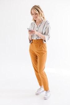 Pełna długość europejska młoda kobieta nosząca zwykłe ubrania, uśmiechająca się i pisząca na telefonie komórkowym na białym tle nad białą ścianą