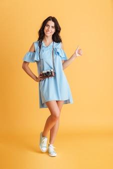 Pełna długość fotografa młodej kobiety w sukience z retro aparatem pokazującym kciuki do góry na białym tle