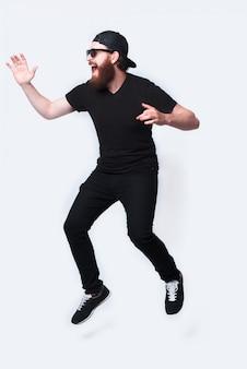 Pełna długość fotografia młodego brodacza mężczyzna doskakiwanie