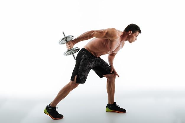 Pełna długość fotografia młody sporty mężczyzna ćwiczy z dumbbell