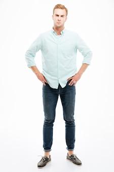 Pełna długość gniewnego surowego młodego mężczyzny stojącego z rękami na biodrach