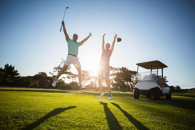 Pełna długość golfa para graczy z podniesionymi rękami