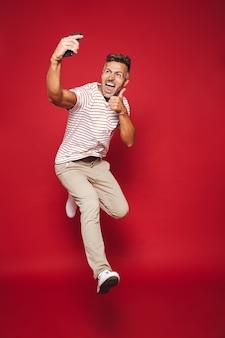 Pełna długość kaukaskiego mężczyzny w pasiastym t-shircie skaczącym i robiącym selfie na telefonie komórkowym odizolowanym na czerwono