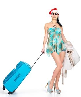Pełna długość kobiety w santa hat stojącej z walizką podróżną