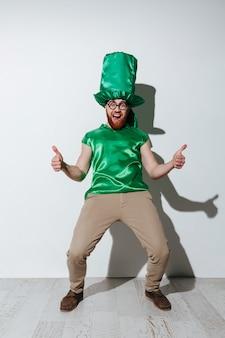 Pełna długość krzyczącego mężczyzny w zielonym stroju