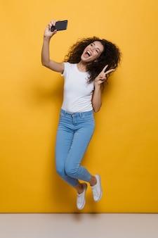 Pełna długość ładnej kobiety w wieku 20 lat z kręconymi włosami, trzymającej smartfona i robiącej zdjęcie selfie izolowane na żółto