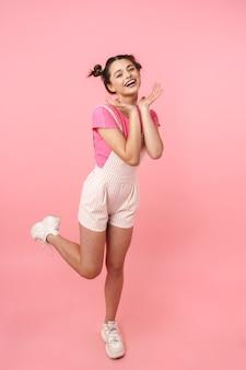 Pełna długość ładnej młodej nastolatki skaczącej odosobnionej, radującej się