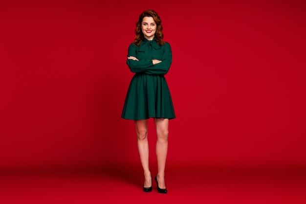 Pełna długość ładnej wesołej dziewczyny z założonymi rękami na czerwonym tle