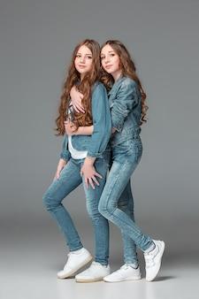Pełna długość młoda szczupła żeńska dziewczyna w drelichowych dżinsach na szarości ścianie