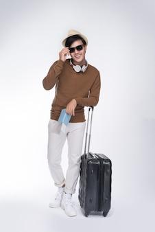 Pełna długość młodego turysty azjatyckiego mężczyzny trzymającego paszport z walizką na szarym tle