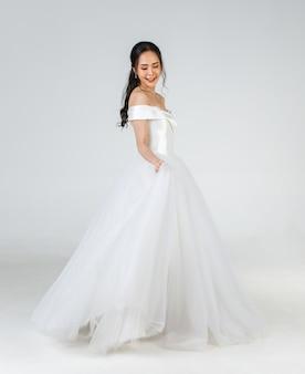 Pełna długość młodej atrakcyjnej azjatyckiej kobiety, która wkrótce zostanie panną młodą, ubrana w białą suknię ślubną wyglądającą na szczęśliwego przędzenia. koncepcja fotografii przedślubnej.