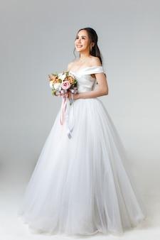 Pełna długość młodej atrakcyjnej azjatyckiej kobiety, która wkrótce zostanie panną młodą, ubrana w białą suknię ślubną wyglądającą na szczęśliwego trzymania bukietu kwiatów. koncepcja fotografii przedślubnej.