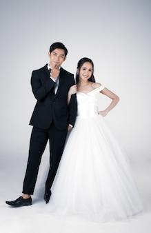 Pełna długość młodej atrakcyjnej pary azjatyckiej, wkrótce młodej pary, kobieta ubrana w białą suknię ślubną. mężczyzna ubrany w czarny smoking, stojący razem. koncepcja fotografii przedślubnej.