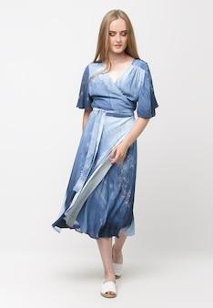 Pełna długość młodej eleganckiej dziewczyny w jasnoniebieskiej letniej sukience na jasnym tle