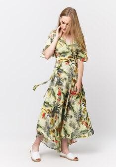 Pełna długość młodej eleganckiej dziewczyny w lekkiej letniej sukience na jasnym tle