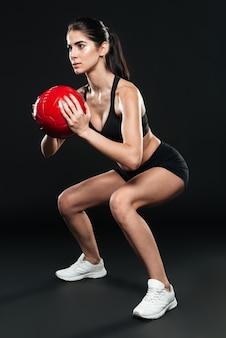 Pełna długość młodej kobiety fitness wykonującej przysiady z ciężarem na czarnej ścianie