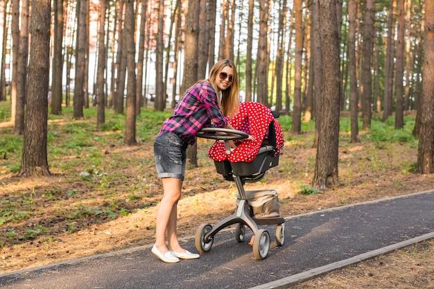Pełna długość młodej matki pchającej wózek w parku