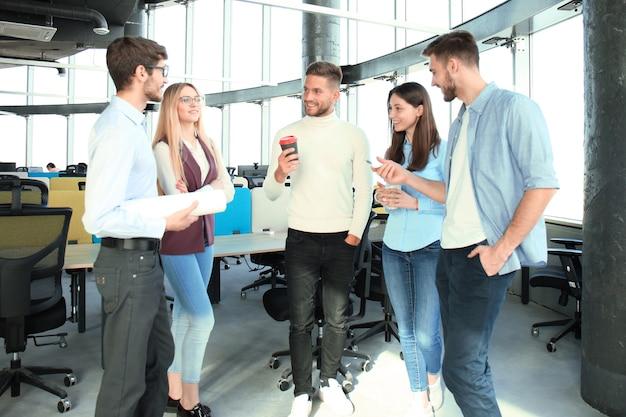 Pełna długość młodych ludzi w eleganckich strojach casualowych, rozmawiających o biznesie i uśmiechających się podczas spaceru po biurze.