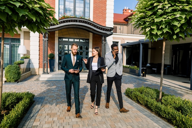 Pełna długość młodych trzech uśmiechniętych wielorasowych biznesmenów omawiających spotkanie podczas spaceru na świeżym powietrzu przed nowoczesnym budynkiem, biurem, restauracją lub hotelem