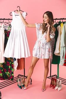 Pełna długość modnej kobiety w sukience stojącej obok garderoby z ubraniami i wybierającej w co się ubrać na różowym tle
