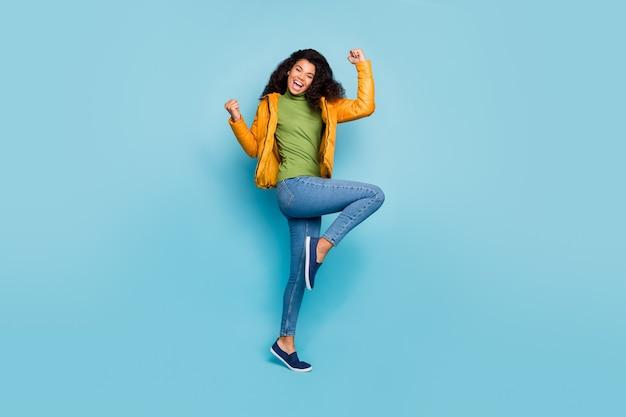 Pełna długość niesamowita ciemna skóra kręcona dama ekstatyczna dobra ciepła jesień pogoda spacerowa odzież uliczna żółty wiosenny płaszcz dżinsy zielony sweter izolowany niebieski kolor ściana
