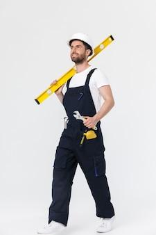 Pełna długość pewnego siebie brodatego budowniczego mężczyzny w kombinezonie i kasku stojącym na białym tle nad białą ścianą, niosącego poziom pomiaru