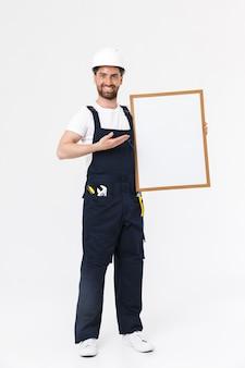 Pełna długość pewnego siebie brodatego budowniczego mężczyzny w kombinezonie i kasku stojącym na białym tle nad białą ścianą, pokazującym pustą tablicę