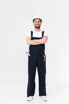 Pełna długość pewnego siebie brodatego budowniczego mężczyzny w kombinezonie i kasku stojącym na białym tle nad białą ścianą, z założonymi rękami