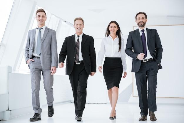 Pełna długość pewni siebie ludzie biznesu chodzą w biurze