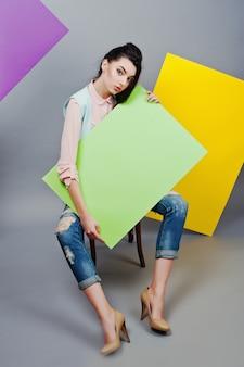 Pełna długość piękna dziewczyna siedzi, trzymając zieloną pustą tablicę reklamową, na szarym tle i żółty i fioletowy transparent