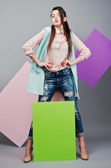 Pełna długość pięknej dziewczyny, z zieloną pustą tablicą reklamową, na szarym tle i różowym i fioletowym sztandarem