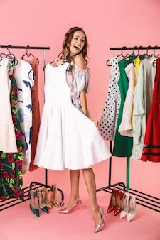 Pełna długość pięknej kobiety w sukience stojącej obok garderoby z ubraniami i wybierającej w co się ubrać na różowym tle