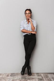 Pełna długość pięknej młodej kobiety afrykańskiego biznesu stojącej