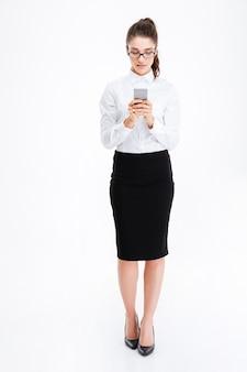 Pełna długość pięknej młodej kobiety biznesu w okularach stojącej i używającej smartfona na białej ścianie