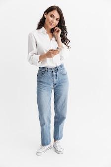 Pełna długość pięknej młodej kobiety z długimi kręconymi włosami brunetki, ubrana w białą koszulę stojącą na białym tle nad białą ścianą, cieszącą się słuchaniem muzyki przez słuchawki, trzymającą telefon komórkowy