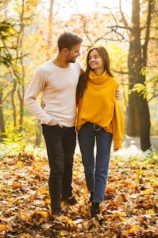 Pełna długość pięknej młodej pary zakochanej spacerującej po jesiennym parku, trzymającej się za ręce