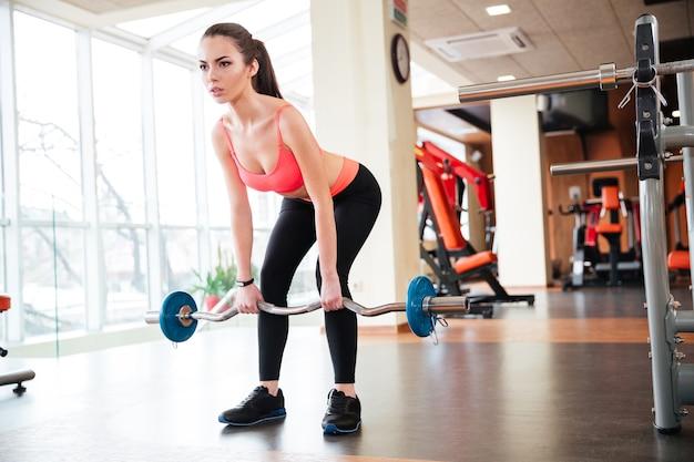 Pełna długość pięknej młodej sportsmenki robi ćwiczenia ze sztangą w siłowni