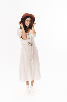 Pełna długość pięknej, szczęśliwej, uroczej młodej brunetki, ubranej w letnią sukienkę i kapelusz stojący na białym tle nad białą ścianą, pozowanie