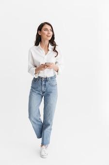 Pełna długość pięknej uśmiechniętej młodej kobiety z długimi kręconymi włosami brunetki, ubrana w białą koszulę stojącą na białym tle nad białą ścianą, korzystająca z telefonu komórkowego