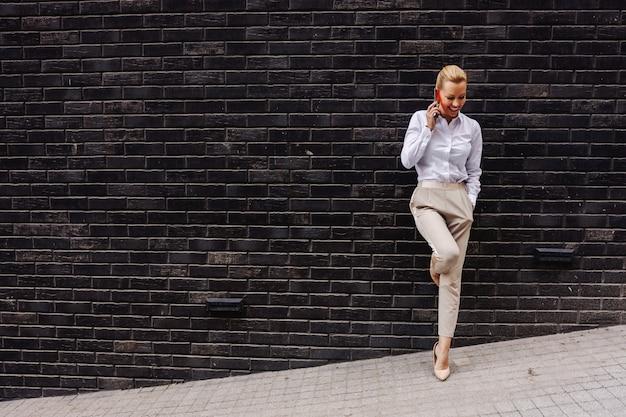 Pełna długość pięknej uśmiechniętej wesołej blond bizneswoman opierającej się o ścianę i rozmawiającej przez telefon.