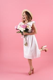 Pełna długość pięknej, wesołej młodej blondynki w letniej sukience, stojącej odizolowanej nad różową ścianą, trzymającej bukiet piwonii, pozującej